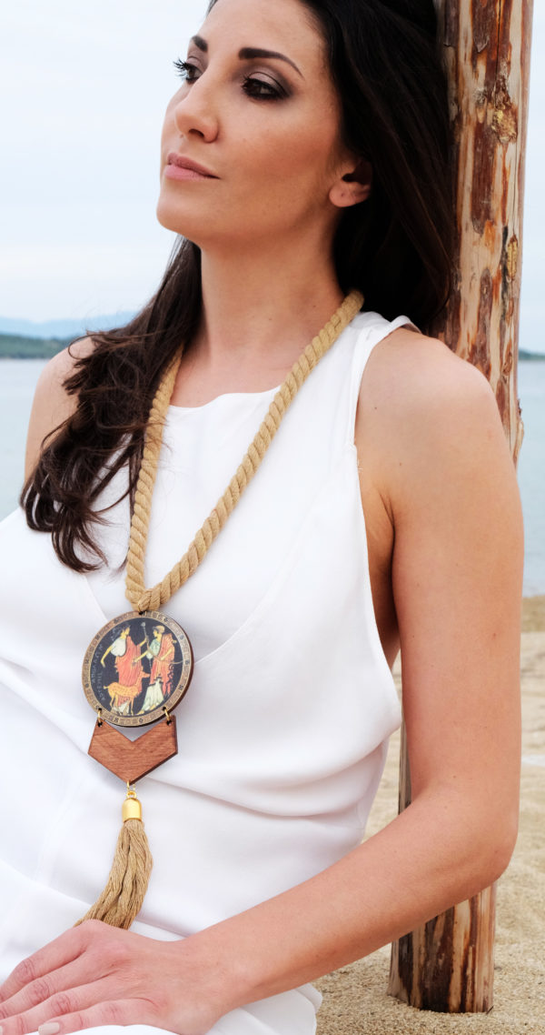a woman is wearing apollo and artemis necklace 1