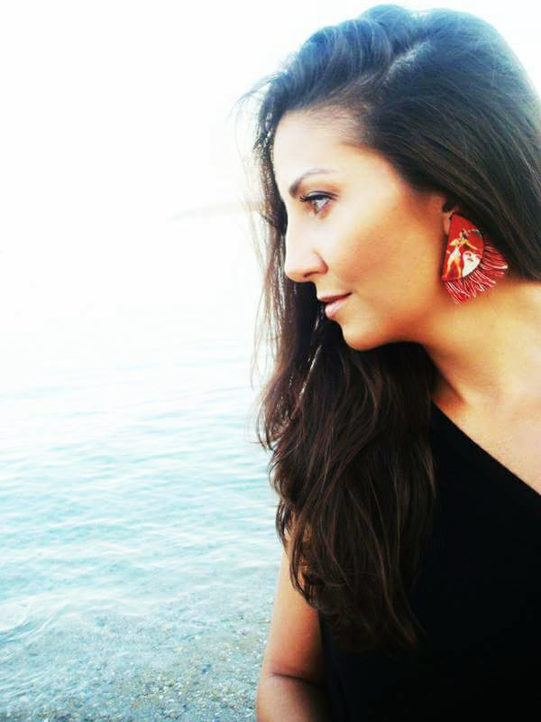 a woman is wearing the prince of lilies red earrings product