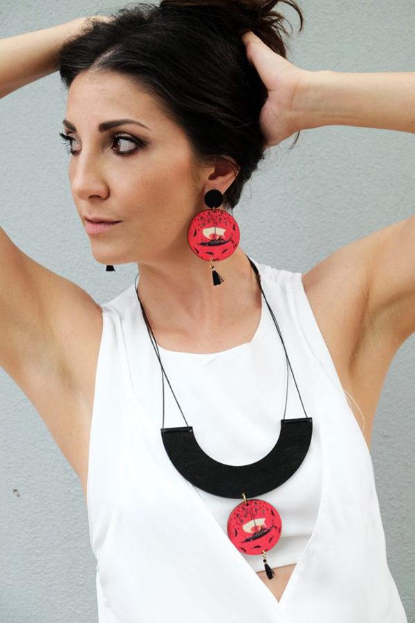 a woman is wearing the srossing the wine sea earrings 3